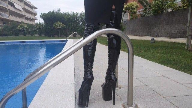 Mamma con gli stivali vista calda tacchi alti vicino alla piscina