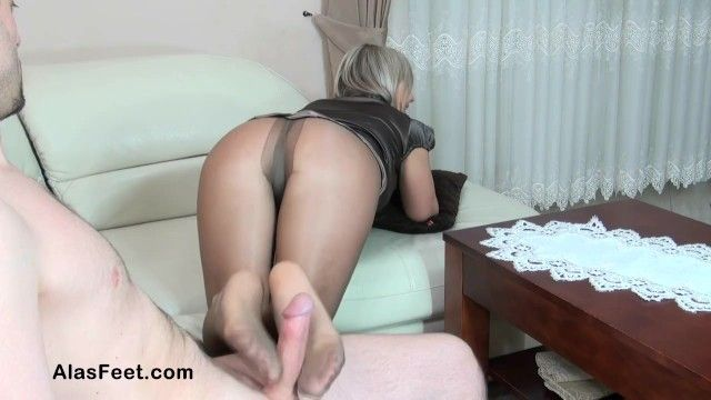 Sexy golden-haired milf in hose gives footjob