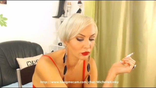 Milf bionda dai capelli corti che fuma una sigaretta sulla webcam